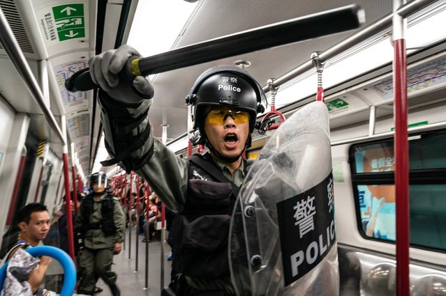 """Riot police charge in a train at the Tung Chung MTR station after protesters block the transport routes to the Hong Kong International Airport on September 1, 2019 in Hong Kong, China. Pro-democracy protesters have continued rallies on the streets of Hong Kong against a controversial extradition bill since 9 June as the city plunged into crisis after waves of demonstrations and several violent clashes. Hong Kong's Chief Executive Carrie Lam apologized for introducing the bill and declared it """"dead"""", however protesters have continued to draw large crowds with demands for Lam's resignation and completely withdraw the bill. (Photo by Anthony Kwan/Getty Images)"""