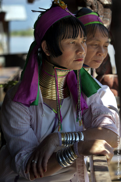 Burmese Long Neck wait for tourists to arrive at a handicraft shop on Inle Lake