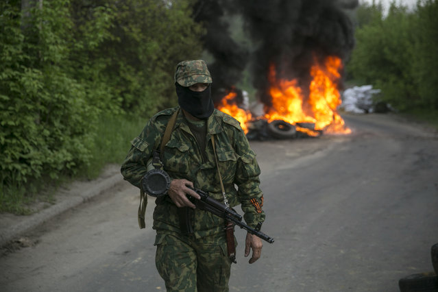 """A pro-Russian separatist guards a checkpoint as tyres burn behind him near the town of Slaviansk in eastern Ukraine May 2, 2014. Ukraine launched a """"large-scale operation"""" to retake the eastern town of Slaviansk, pro-Russian separatists there said on Friday, in an escalation of violence in what has become the worst confrontation between Russia and the West since the Cold War. (Photo by Baz Ratner/Reuters)"""