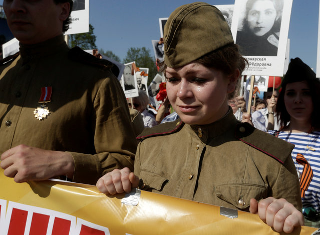 A woman cries as she takes part in the Immortal Regiment march during the Victory Day celebrations in Riga, Latvia, May 9, 2016. (Photo by Ints Kalnins/Reuters)
