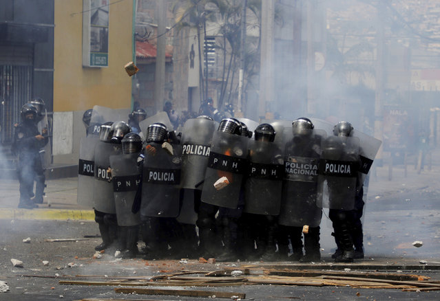 Police stand in riot gear as they face demonstrators during a protest demanding the resignation of President Juan Orlando Hernandez, in Tegucigalpa, Honduras, Sunday, September 15, 2019. Thousands of Hondurans are demanding the resignation of Hernandez. (Photo by Elmer Martinez/AP Photo)