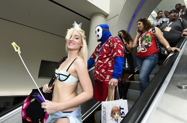 Costumed characters ride the escalator on the second day of the 2015 Comic-Con International held at the San Diego Convention Center Friday, July 10, 2015, in San Diego. (Photo by Denis Poroy/Invision/AP Photo)