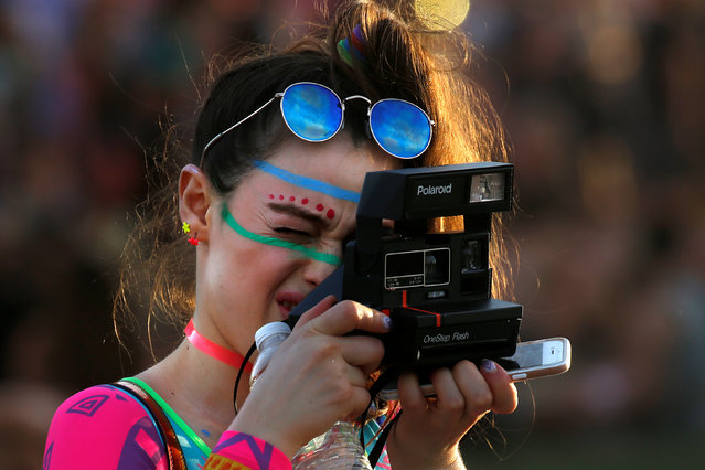 A woman takes a photo with a Polaroid camera during the Coachella Valley Music and Arts Festival on April 17, 2017 in Indio, California. (Photo by Carlo Allegri/Reuters)