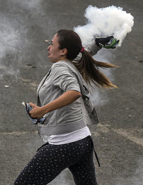 A demonstrator clashes with the riot police during a protest against Venezuelan President Nicolas Maduro, in Caracas on April 20, 2017. (Photo by Juan Barreto/AFP Photo)