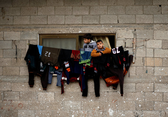 Palestinian boys look out of their family house following heavy rain in a neighbourhood in the northern Gaza Strip February 16, 2017. (Photo by Mohammed Salem/Reuters)