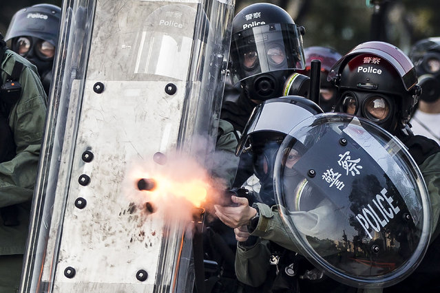 """Riot police fire projectiles against protesters in the Sha Tin district of Hong Kong on October 1, 2019, as violent demonstrations take place in the streets of the city on the National Day holiday to mark the 70th anniversary of communist China's founding. Strife-torn Hong Kong on October 1 marked the 70th anniversary of communist China's founding with defiant """"Day of Grief"""" protests and fresh clashes with police as pro-democracy activists ignored a ban and took to the streets across the city. (Photo by Isaac Lawrence/AFP Photo)"""