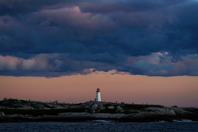 People walk on the rocks at the lighthouse at dusk in Peggy's Cove, Nova Scotia, Canada, August 11, 2019. (Photo by Carlo Allegri/Reuters)