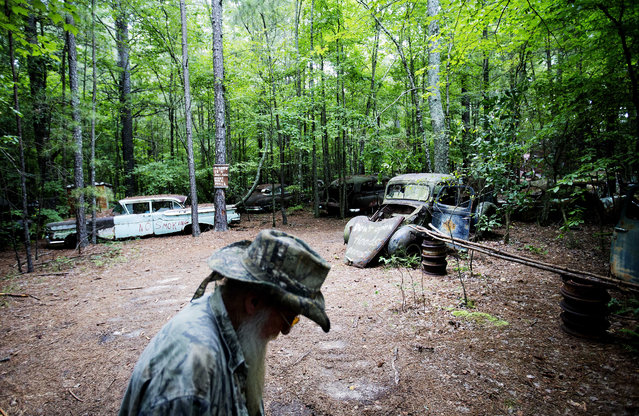 Eddie McDaniel, who goes by Fast Eddie, walks through Old Car City, the world's largest known classic car junkyard, where he occasionally plays piano for visitors Thursday, July 16, 2015, in White, Ga. (Photo by David Goldman/AP Photo)