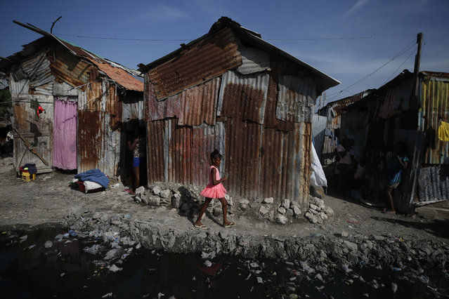 A girl walks between homes and a pool of waste water, used as a toilet by residents who have no access to plumbing in the Cite Soleil district of Port-au-Prince, Haiti, Wednesday, October 9, 2019. Residents of Cite Soleil say access to basic services, jobs, and security has been declining and many are participating in protests calling for the resignation of President Jovenel Moise. (Photo by Rebecca Blackwell/AP Photo)