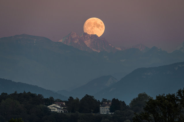 A near full moon rises behind The French Alps as seen from Geneva on September 12, 2019. (Photo by Fabrice Coffrini/AFP Photo)