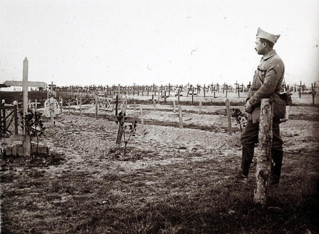 An archive picture shows a French officer standing near a cemetery with recent graves of soldiers killed on the front lines of World War One (WWI), at Saint-Jean-sur-Tourbe on the Champagne front, eastern France December 19, 1916. (Photo by Collection Odette Carrez/Reuters)