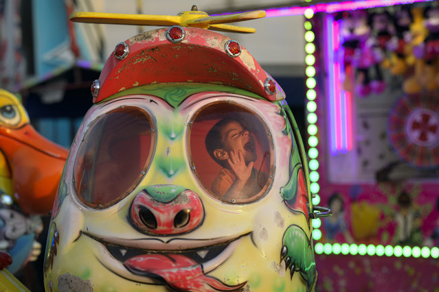 In this picture taken Thursday, September 12, 2019, a child laughs while on a ride at an autumn fair in Titu, southern Romania. Romania's autumn fairs are a loud and colorful reminder that summer has come to an end and, for many families in poorer areas of the country, one of the few affordable public entertainment events of the year. (Photo by Andreea Alexandru/AP Photo)