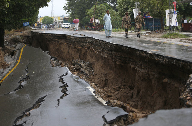 Pakistani army soldiers walk past a damaged portion of a road caused by a powerful earthquake in Jatla near Mirpur, in northeast Pakistan, Wednesday, September 25, 2019. Mourners were burying their dear ones in Pakistan-held Kashmir where a powerful earthquake struck a day before. (Photo by Anjum Naveed/AP Photo)
