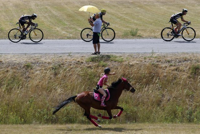 A girl rides a horse as the break away group of riders passes during the 161-km (100 miles) 17th stage of the 102nd Tour de France cycling race from Digne-les-Bains to Pra Loup in the French Alps mountains, France, July 22, 2015. (Photo by Stefano Rellandini/Reuters)