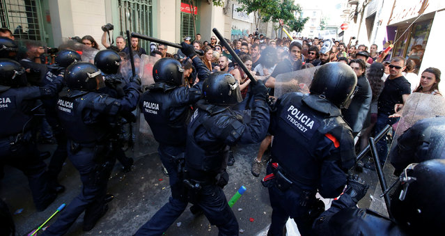 """Catalan regional police in full riot gear charge demonstrators during a protest over the eviction of squatters earlier in the week from """"The Expropriated Bank"""", in Barcelona, Spain, May 29, 2016. (Photo by Albert Gea/Reuters)"""