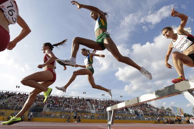 Athletes clear an obstacle as they competes  in the women's 3000 meters steeplechase during the Pan Am Games Friday, July 24, 2015, in Toronto. (Photo by Gregory Bull/AP Photo)