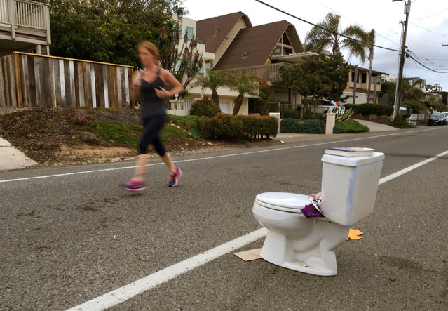 An early morning runner jogs past a toilet placed on the side of the road for free pick-up to any passerby in Leucadia, California, United States May 24, 2016. (Photo by Mike Blake/Reuters)