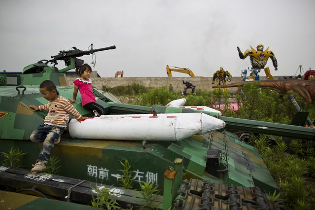 """Children play on a """"Transformers"""" replica on the outskirts of Shanghai, June 18, 2014. Li Lei, owner of a small factory, uses his spare time and money to build """"Transformers"""" replicas for rent or sale. The new Transformers movie, which is premiering later this month, has brought the factory many new orders, according to Li. (Photo by Aly Song/Reuters)"""