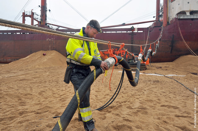 An employee of Dutch company SMIT fixes a pipe during oil pumping operations on the TK Bremen, on December 19, 2011