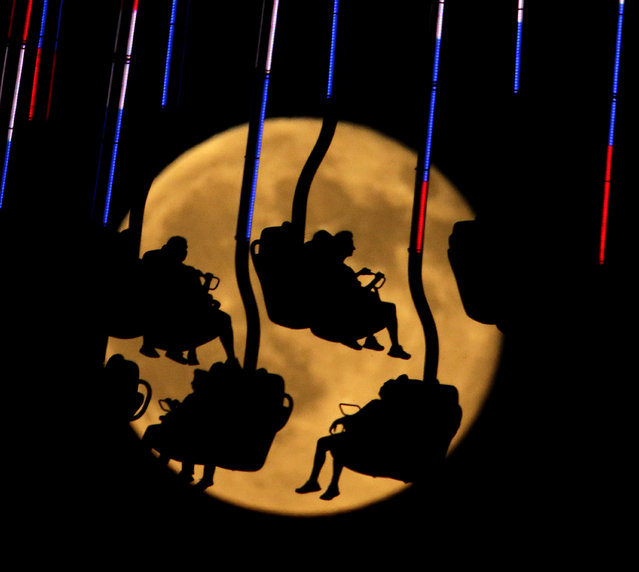 People are silhouetted against a rising blue moon as they ride an attraction at Worlds of Fun amusement park camp Friday, July 31, 2015, in Kansas City, Mo. A blue moon happens when the moon rises in its full stage twice during the same month. (Photo by Charlie Riedel/AP Photo)