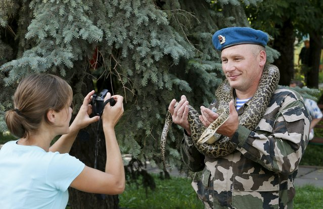 A former paratrooper poses for a picture with a python during celebrations for the Paratroopers Day at the Central park in the Siberian city of Krasnoyarsk, Russia, August 2, 2015. (Photo by Ilya Naymushin/Reuters)