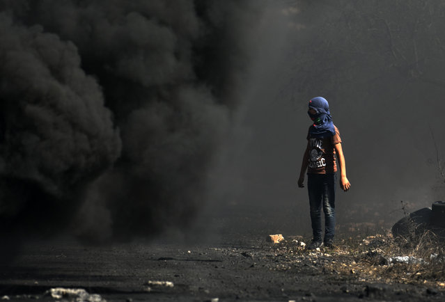 A Palestinian demonstrator watches as smoke billows from a fire during clashes with Israeli forces following a weekly protest against the expropriation of Palestinian land by Israel, in the village of Kfar Qaddum, in the Israeli-occupied West Bank on October 11, 2019. (Photo by Jaafar Ashtiyeh/AFP Photo)