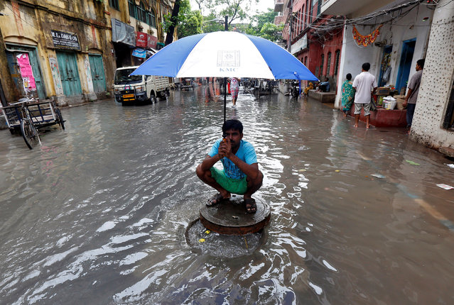 A municipal worker sits on the cover of a manhole after uncovering it on a flooded street after heavy rains in Kolkata, June 20, 2017. (Photo by Rupak De Chowdhuri/Reuters)