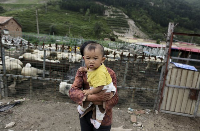 A local villager holds her grandson outside her sheepfold near Dolomiti Mountain Resort in Chongli county of Zhangjiakou, jointly bidding to host the 2022 Winter Olympic Games with capital Beijing, July 31, 2015. (Photo by Jason Lee/Reuters)