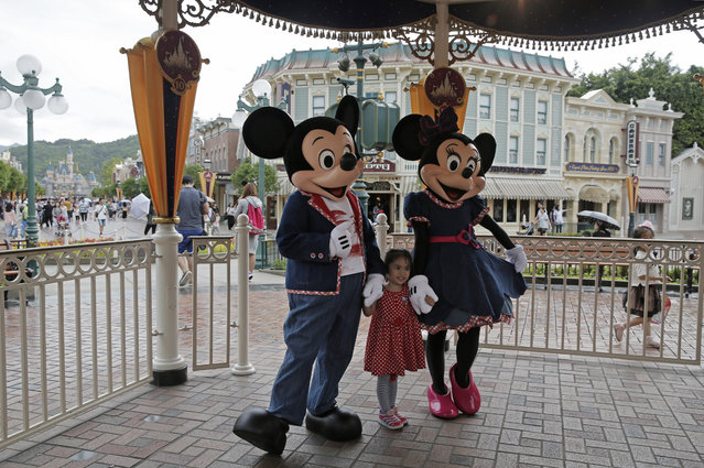 In this Friday, June 10, 2016 photo, a girl poses with Mickey Mouse and Minnie Mouse at the Hong Kong Disneyland. (Photo by Kin Cheung/AP Photo)