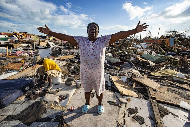 "Aliana Alexis of Haiti stands on the concrete slab of what is left of her home after destruction from Hurricane Dorian in an area called ""The Mud"" at Marsh Harbour in Great Abaco Island, Bahamas on September 5, 2019. (Photo by Al Diaz/Zuma Press via AFP Photo)"
