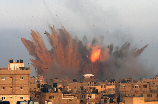 A ball of fire is seen following an Israeli air strike, on July 11, 2014 in Rafah, in the southern of Gaza Strip. Israeli warplanes kept up deadly raids on Gaza but failed to stop Palestinian militants firing rockets across the border, as the United States offered to help negotiate a truce. (Photo by Said Khatib/AFP Photo)