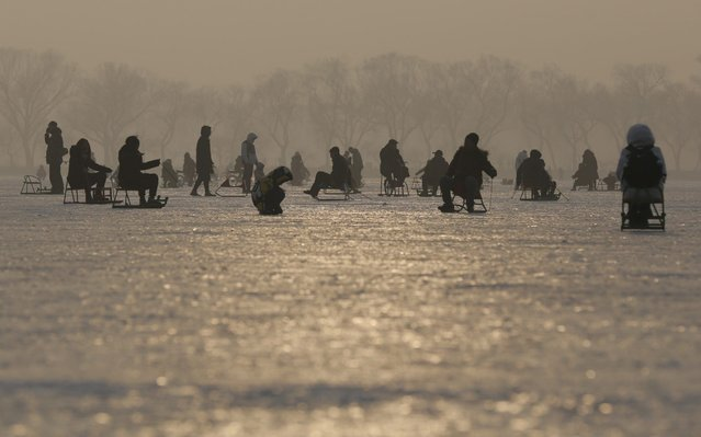 Chinese people sit on chairs outfitted with ice skates on the frozen surface of Kunming Lake of the Summer Palace in Beijing, China, 18 January 2020. Chinese people skate and enjoy their leisure time on the frozen lake during the winter season. (Photo by Wu Hong/EPA/EFE/Rex Features/Shutterstock)