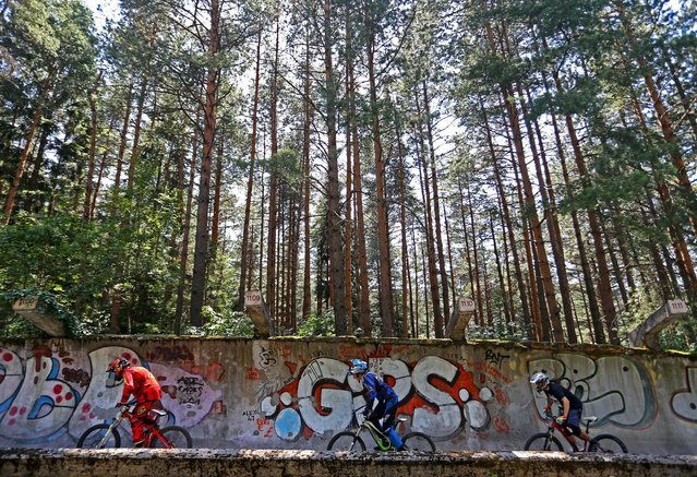 Downhill bikers Kemal Mulic (L-R), Kamer Kolar and Tarik Hadzic train on the disused bobsled track from the 1984 Sarajevo Winter Olympics on Trebevic mountain near Sarajevo, Bosnia and Herzegovina, August 8, 2015. (Photo by Dado Ruvic/Reuters)