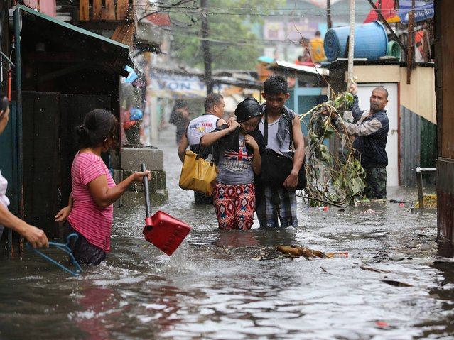 Residents wade through floods as they go back to their home while Typhoon Rammasun batters suburban Quezon city, north of Manila, Philippines on Wednesday, July 16, 2014. Typhoon Rammasun knocked out power in many areas but it spared the Philippine capital, Manila, and densely-populated northern provinces from being directly battered Wednesday when its fierce wind shifted slightly away, officials said. (Photo by Aaron Favila/AP Photo)