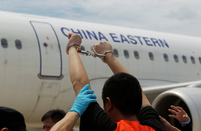 A suspect of telecom fraud lifts his hands up as he is deported to China at the International Airport of Phnom Penh, Cambodia June 24, 2016. (Photo by Samrang Pring/Reuters)