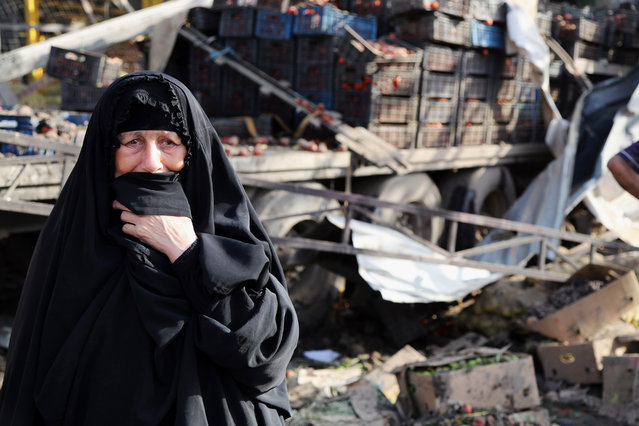 An Iraqi woman grieves at the scene of a bomb attack in Jameela market in the Iraqi capital's crowded Sadr City neighborhood Baghdad, Iraq, Thursday, August 13, 2015. A massive truck bomb ripped through a popular Baghdad food market in a predominantly Shiite neighborhood in the early morning hours on Thursday, killing dozens of people, police officials said. (Photo by Karim Kadim/AP Photo)