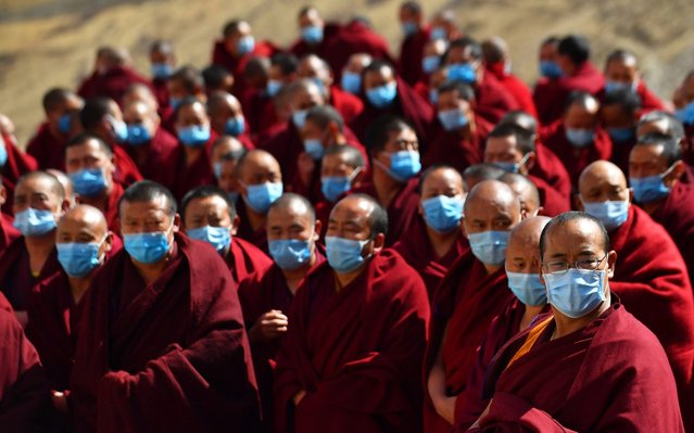 Monks attend a prayer service for blessing at the Gandan Temple in Lhasa, capital of southwest China's Tibet Autonomous Region, February 5, 2020. Tibetan Buddhist temples held prayer services to support novel coronavirus-infected areas in China. The monks here were also organized to donate money to help fight against the epidemic. (Photo by Chogo/Xinhua News Agency)