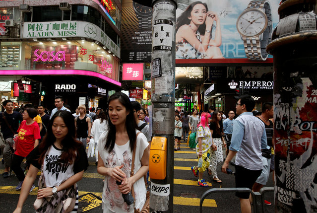 Shoppers cross a street at the Causeway Bay shopping district in Hong Kong July 22, 2014. (Photo by Bobby Yip/Reuters)