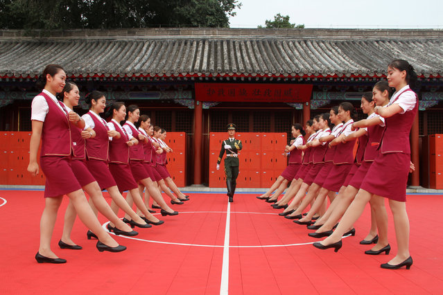 Train attendants take part in a parade training as they visit the national flag guard during a patriotic education event ahead of the 90th anniversary of the founding of the Chinese People's Liberation Army (PLA) in Beijing, China July 25, 2017. (Photo by Reuters/China Stringer Network)