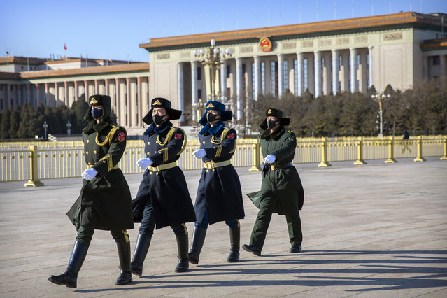 In this February 4, 2020, file photo, members of a Chinese honor guard wear face masks as they march in formation near the Great Hall of the People on Tiananmen Square in Beijing. China's ruling Communist Party faces a politically fraught decision: Admit the outbreak of a new virus isn't under control and cancel this year's highest-profile official event. Or bring 3,000 legislators to Beijing next month and risk fueling public anger at the government's handling of the disease. (Photo by Mark Schiefelbein/AP Photo/File)