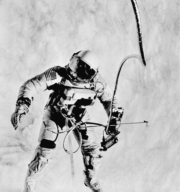 """Astronaut Ed White faces the Gemini 4 capsule during his 20-minute space """"walk"""" on June 8, 1965.  In his right hand, White holds his oxygen space gun to maneuver around the capsule.  A 35-mm camera is attached to the space gun.  Astronaut James McDivitt  took this photograph with a Hasselblad camera. (Photo by James McDivitt/AP Photo/NASA)"""
