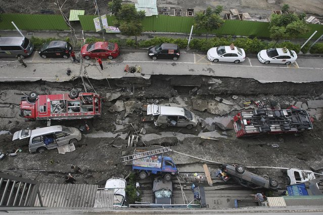Vehicles are left lie in a destroyed street following multiple explosions from an underground gas leak in Kaohsiung, Taiwan, early Friday, Aug. 1, 2014. A massive gas leakage early Friday caused five explosions that killed scores of people and injured over 200 in the southern Taiwan port city of Kaohsiung. (Photo by AP Photo)