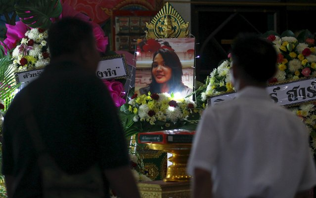 """Relatives look at a picture of Thai victim from Monday's bomb blast, Waraporn Changtam, while praying during a Buddhist funeral at a temple in Nonthaburi province, on the outskirts of Bangkok, Thailand, August 19, 2015. Thai police on Wednesday issued an arrest warrant for an individual they described as a """"foreign man"""", in connection with a bomb blast in Bangkok that killed 20 people, including many foreigners. (Photo by Chaiwat Subprasom/Reuters)"""