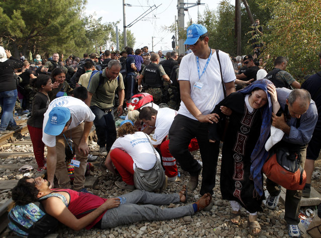 UNHCR workers help migrants who have collapsed while the crowd of migrants were pushing the police to enter into Macedonia, at the railway tracks on border line with Greece, near the southern Macedonia's town of Gevgelija, on Friday, August 21, 2015. (Photo by Boris Grdanoski/AP Photo)