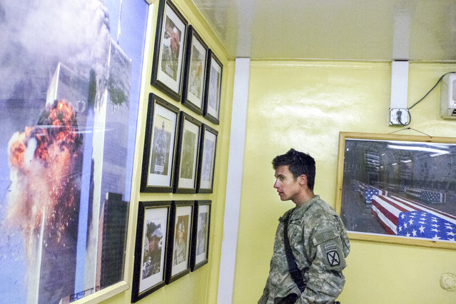 """Lieutenant Erik Malmstrom looks at photos of three fallen soldiers from his brigade. His brigade lost more men than any single unit in Afghanistan. """"To have a hope of succeeding (in Afghanistan) you have to be part warrior, part anthropologist, part diplomat, part development worker"""", Malmstrom told Van Agtmael. (Photo and caption by Van Agtmael/Harrison Jacobs/Magnum Photos)"""