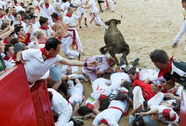 A wild cow jumps over revelers in the bullring after the first running of the bulls at the San Fermin festival in Pamplona, northern Spain, July 7, 2016. (Photo by Eloy Alonso/Reuters)