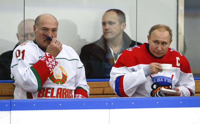"""In this Friday, February 7, 2020 file photo, Russian President Vladimir Putin, right, and Belarusian President Alexander Lukashenko take a break during a match of the Night Hockey League teams in Rosa Khutor in the Black Sea resort of Sochi, Russia. Lukashenko on Friday, Feb. 14 says Russia insisted on merging the two states during last week's talks on further integrating the countries' economies. He says """"this isn't integration, it's incorporation"""". Tension has been running high between the neighboring ex-Soviet states for several months now. (Photo by Alexander Zemlianichenko/AP Photo/File)"""