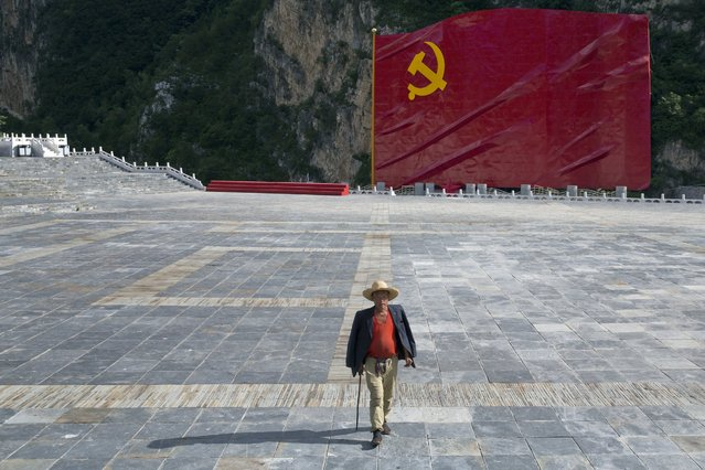 A man walks in front of a giant sculpture depicting a Communist Party of China flag near a museum on the outskirts of Beijing Thursday, June 30, 2016. July 1, 2016 marks the 95th anniversary of the founding of the Communist Party of China. (Photo by Ng Han Guan/AP Photo)