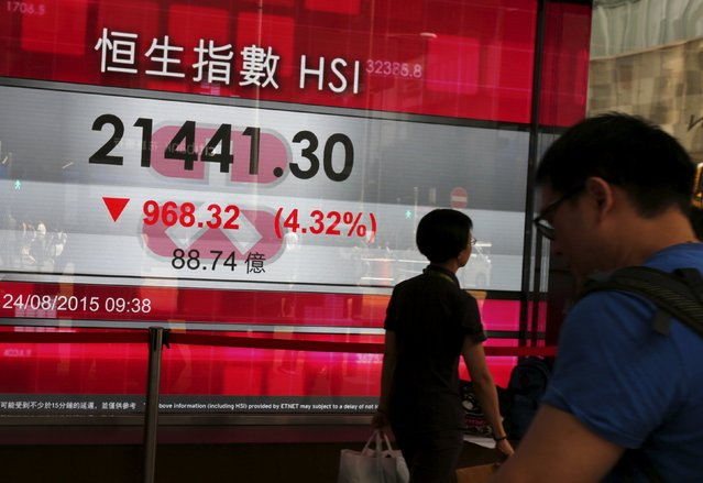 Passersby walk past a panel displaying the Hang Seng Index, which drops more than four percent during morning trading, at the financial Central district in Hong Kong, China August 24, 2015. (Photo by Bobby Yip/Reuters)