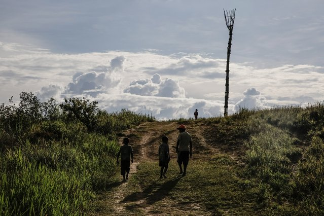 Boys from the Dani tribe walk on a field at Soroba Village on August 9, 2014 in Wamena, Papua, Indonesia. (Photo by Agung Parameswara/Getty Images)